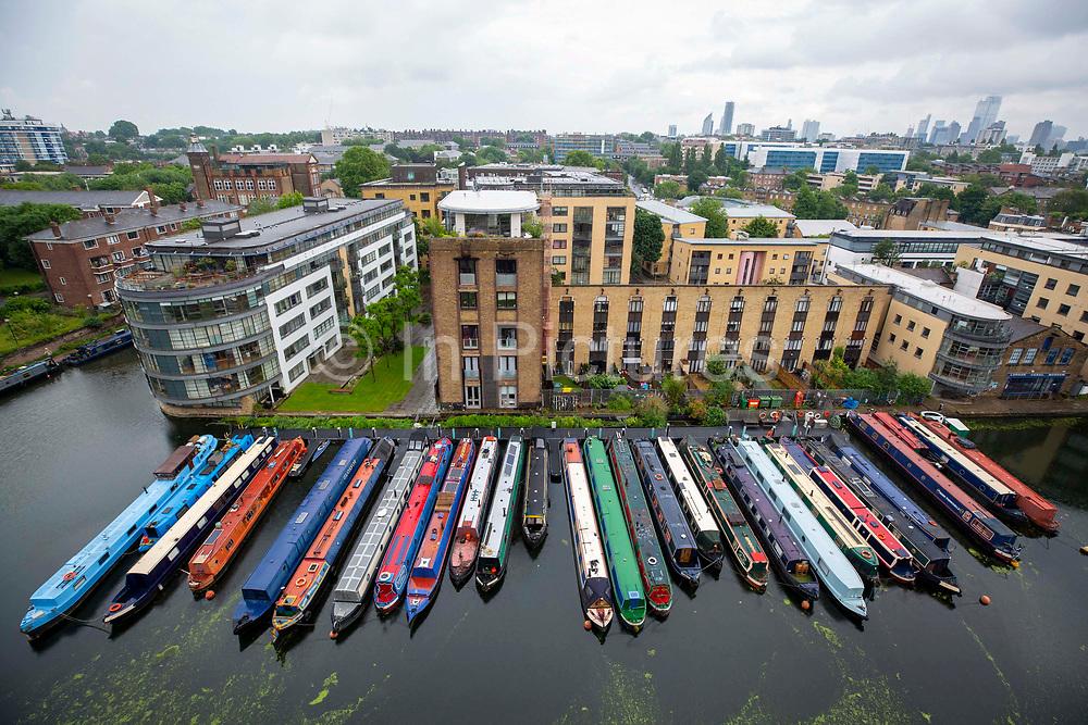 A line of narrow boats moored in the Battlebridge Basin on Regents Canal. Kings Cross, London, United Kingdom.