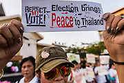"""12 JANUARY 2014 - BANGKOK, THAILAND: A woman holds up sign supporting Thai democracy during a candlelight vigil at Thammasat University in Bangkok. About 500 people from all walks of Thai life came to a candlelight vigil at Thammasat University. They prayed for a peaceful resolution to the political conflict in Thailand. They finished the vigil by singing the John Lennon song """"Imagine."""" Anti-government protestors are expected """"Shutdown Bangkok"""" Monday. There were reports Sunday evening that some intersections were already being blocked.       PHOTO BY JACK KURTZ"""