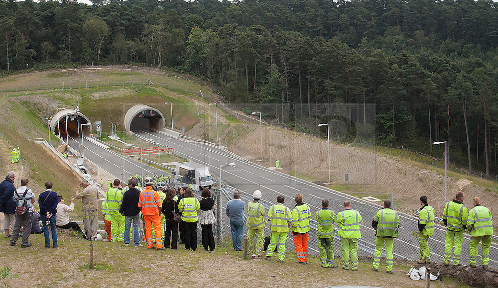 © Licensed to London News Pictures. 27/07/2011. Hindhead, Surrey, UK. Today (Wednesday) The £371 Million Hindhead Tunnel project officially opens to the public.  Pictured: Some of the construction team and members of the public await the first traffic after it is unvelied by the Secretary of State for Transport RT Honorable Phillip Hammond MP.S Photo credit: Sam Spickett/LNP