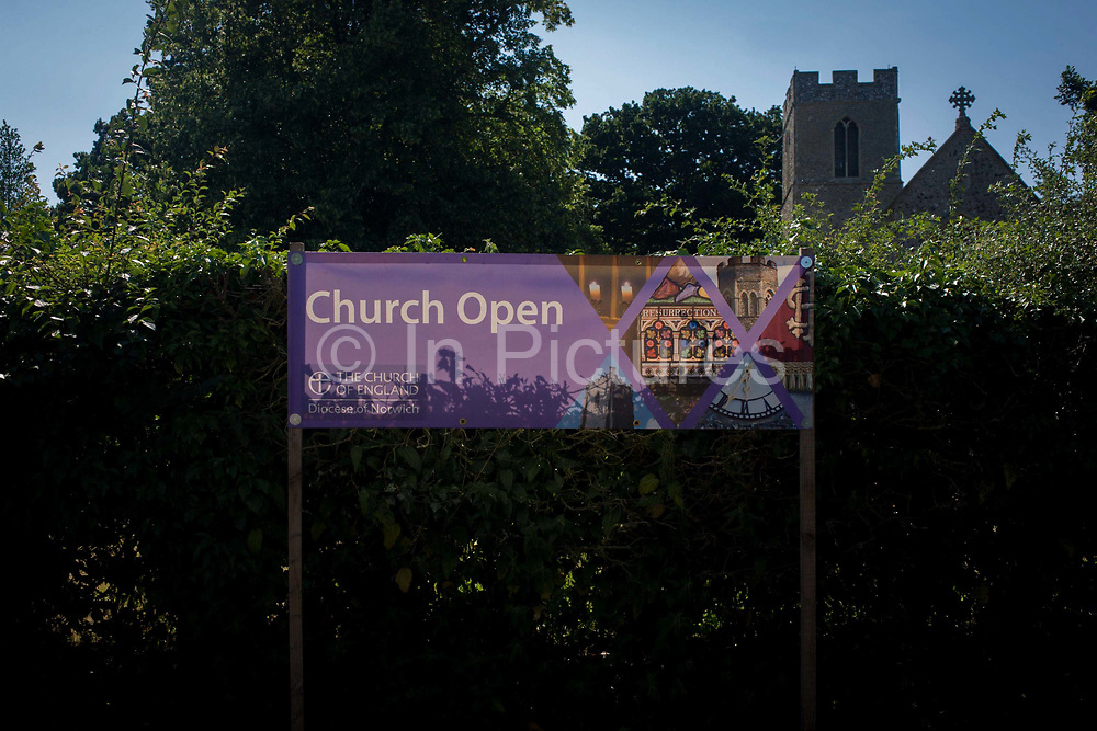 A 'church Open' banner on display outside the flint wall architecture of St Michael's Anglican church at Irstead, on the Norfolk Broads. With a tall hedge shielding the church property from a nearby lane, the low spire and cross ardorning the nave rise above the protective shrub. This area of Britain is known as East Anglia, once the stronghold of Saxon tribes then later, of Norse Vikings before Christianity dominated the religious landscape. Christian sites of worship were built on pagan shrines to encourage the following of the new God.
