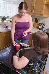 Non disabled woman making a drink for her friend who is a person with a disability,  The condition means it's necessary for the woman to drink through a straw,