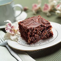 Fudge brownie served on fine china and a doily.