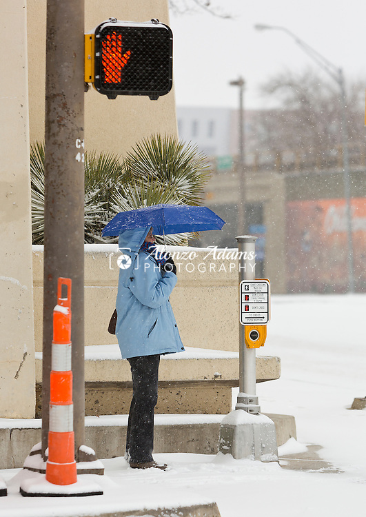 A woman waits to cross the street during a snow shower in downtown Oklahoma City on Saturday, Feb. 2, 2014.  (Photo copyright © 2014 Alonzo J. Adams)