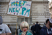 On the day that the new Conservative Party leader Theresa May MP became Prime Minister of the UK, protesters humorously dressed up in face masks and singing amusing political songs mocking the PM outside Downing Street on 13th July 2016 in London, United Kingdom. The leader of the protest dressed up as a joke Theresa May with blonde wig, crudely put on make up, see through plastic dress and wearing pearls, delighted passers by. photo by /In Pictures via Getty Images
