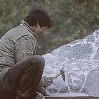 "NEPAL, HIMALAYA. Sherpa stonecarver carving a boulder into a ""mani stone"" with Tibetan Buddhist prayers."