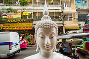 "12 NOVEMBER 2012 - BANGKOK, THAILAND:   An unpainted statue of the Buddha for sale on  Bamrung Muang Street in Bangkok. Thanon Bamrung Muang (Thanon is Thai for Road or Street) is Bangkok's ""Street of Many Buddhas."" Like many ancient cities, Bangkok was once a city of artisan's neighborhoods and Bamrung Muang Road, near Bangkok's present day city hall, was once the street where all the country's Buddha statues were made. Now they made in factories on the edge of Bangkok, but Bamrung Muang Road is still where the statues are sold. Once an elephant trail, it was one of the first streets paved in Bangkok. It is the largest center of Buddhist supplies in Thailand. Not just statues but also monk's robes, candles, alms bowls, and pre-configured alms baskets are for sale along both sides of the street.    PHOTO BY JACK KURTZ"