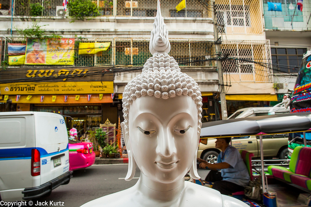 """12 NOVEMBER 2012 - BANGKOK, THAILAND:   An unpainted statue of the Buddha for sale on  Bamrung Muang Street in Bangkok. Thanon Bamrung Muang (Thanon is Thai for Road or Street) is Bangkok's """"Street of Many Buddhas."""" Like many ancient cities, Bangkok was once a city of artisan's neighborhoods and Bamrung Muang Road, near Bangkok's present day city hall, was once the street where all the country's Buddha statues were made. Now they made in factories on the edge of Bangkok, but Bamrung Muang Road is still where the statues are sold. Once an elephant trail, it was one of the first streets paved in Bangkok. It is the largest center of Buddhist supplies in Thailand. Not just statues but also monk's robes, candles, alms bowls, and pre-configured alms baskets are for sale along both sides of the street.    PHOTO BY JACK KURTZ"""