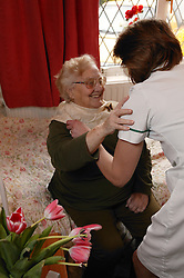 Carer helping an elderly woman with her scarf; homecare for the elderly,