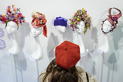 """© Licensed to London News Pictures. 05/04/2019. LONDON, UK. A visitor views creations at """"The Great Hat Exhibition - World Garden"""", which is taking place at the Menier Gallery near London Bridge until 12 April 2019, as part of London Hat Week.  150 international milliners have created 200 hats inspired by the colours, flowers, plants and landscapes from around the world.  The exhibition is curated by Monique Lee Millinery and supported by X Terrace, a fashion platform.  Photo credit: Stephen Chung/LNP"""