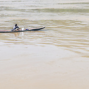 A young man motors his sampan along the  Mekong River near Luang Prabang in central Laos.