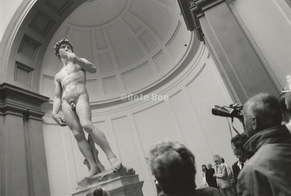 Tourist looking at Michelangelo?s statue of David L'Academia Florence Italy .