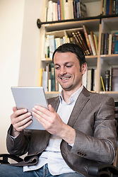 Mature businessman using digital tablet in an office and smiling, Bavaria, Germany