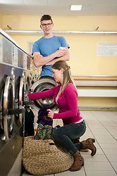 Young couple filling up cloths in washing machine