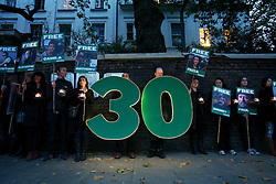Licensed to London News Pictures.<br /> London. UK. <br /> Greenpeace activists hold a candle lit vigil outside the Russian embassy on the 30th day of the detention of the Artic 30, held in a Russian jail. <br /> Photo credit: Anna Branthwaite/LNP