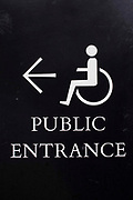 Black and white sign showing the way for disabled members of the public to enter the British Library in London, United Kingdom.  The signs use the International Symbol of Access designed in 1968. The symbol is often seen where access has been improved, particularly for wheelchair users, but also for other disability issues.  Frequently, the symbol denotes the removal of environmental barriers, such as steps, to help also older people, parents with baby carriages, and travelers.