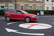 A red vehicle passes a mini-roundabout painted with the St George's flag on 10th July 2021 in Windsor, United Kingdom. The Royal Borough of Windsor and Maidenhead repainted several roundabouts for safety reasons previously daubed with England flags before England's Euro 2020 quarter-final match against Ukraine but it appears that local residents have restored them in advance of the Euro 2020 final between England and Italy.