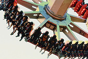 High in the air, people are securely strapped into an amusement park ride.<br /> <br /> Mechanized thrill machines are what makes an amusement park out of a pastoral, relaxing picnic grove or retreat. Earliest rides include the carousel which was originally developed as a way of practicing and then showing-off expertise at tournament skills such as riding and spearing the ring. By the 19th century, carousels were common in parks around the world. Another such ride which shaped the future of the amusement park was the roller coaster. Beginning as a winter sport in 17th century Russia, these gravity driven railroads were the beginning of the search for even more thrilling amusement park rides. The Columbian Exposition of 1893 was a particular fertile testing ground for amusement rides. The Ferris wheel is the most recognized product of the fair.
