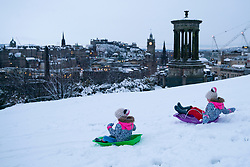 Edinburgh, Scotland, UK. 21 January 2020. Storm Christoph brought overnight snow to Edinburgh. Pic; Sisters Iris and Rosalie from Edinburgh enjoy sledging on Calton Hill infant of famous skyline view. Iain Masterton/Alamy Live News