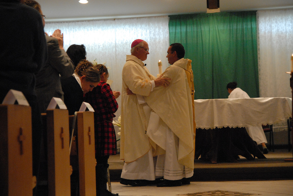 Bishop George Rassas (center) congratulates Fr. Claudio Diaz (right) after installing his as Pastor of Mision San Juan Diego in Arlington Heights.
