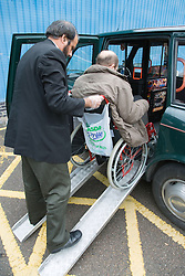 Taxi driver helping wheelchair user into taxi via ramps,