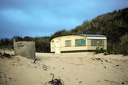 30 June 2020. South of Calais, France.<br /> Smugglers' Paradise. Deserted shacks and a deserted caravan are hidden in the sand dunes of a remote beach south of Calais where local police claim migrants often attempt the treacherous crossing to Great Britain. Items found in a shack and caravan including passport photos, empty water bottles, mattresses and cardboard used as bedding clearly indicate the seemingly derelict premises have recently been used. The location is reasonably remote and backs onto farmland. A gravel access road makes this a prime location for ruthless criminal gangs to drop migrants paying as much as €5,000 for a ticket on an inflatable dinghy with a small outboard motor and less for surfboards and inflatable kayaks. Local police claim it is from here and other beaches in the region that migrants often set out to make desperate and dangerous attempts to cross one of the busiest shipping lanes in the world. Migrants are crossing the English Channel (La Manche) by boat, kayak, surf board and even inflatable paddling pools as numbers seeking asylum in the UK continue to rise. <br /> Photo©; Charlie Varley/varleypix.com