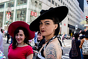 "New York, NY - April 16, 2017. A tattooed woman wears a jaunty black hat at New York's annual Easter Bonnet Parade and Festival on Fifth Avenue. The tattoo is of a perfume bottle labelled ""Oo-la-la."""