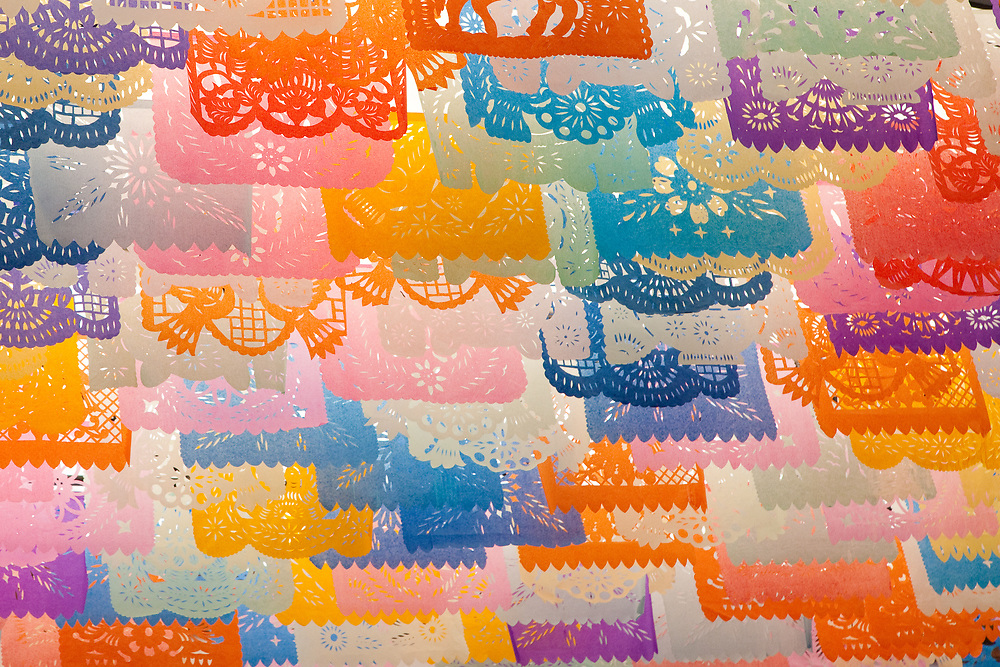 "North America, Mexico, Oaxaca Province, Oaxaca, colorful tissue paper cut-out flags known as ""papel picado"""