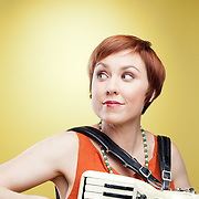 A cute redheaded woman playing an accordian. Photographed with studio light in front of a yellow backdrop.