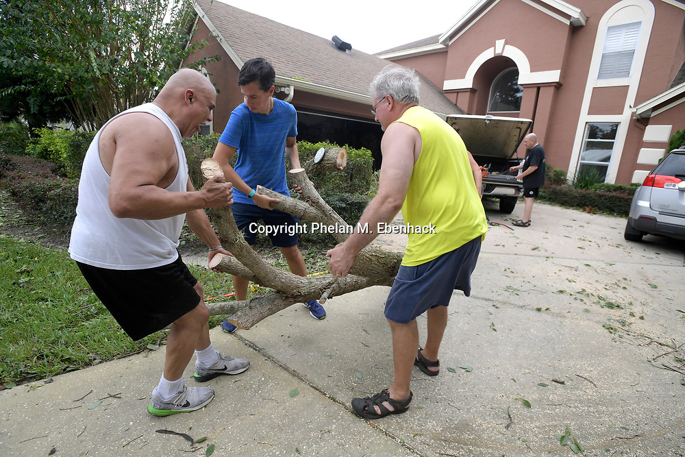 Joe Piriz, left, Bryan Guillette, second from left, and Steve Bontell help remove a cut tree from the front yard of Rick Leseman, right, after Hurricane Irma rolled through Monday, Sept. 11, 2017, in Windermere, Fla. (Photo by Phelan M. Ebenhack)