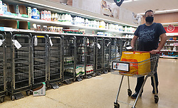 © Licensed to London News Pictures. 07/10/2021. London, UK. A shopper wearing a face covering walks past empty shelves of fresh milk in Sainsbury's, north London just after 9am. The Government and retailers warn that food shortages could continue until Christmas due to labour shortages following Brexit. Photo credit: Dinendra Haria/LNP
