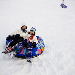 Young girls (age 8) sledding at Wagon Hill Farm in Durham, New Hampshire.