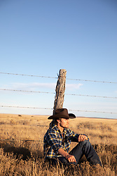 cowboy at sunset sitting by a rustic fence