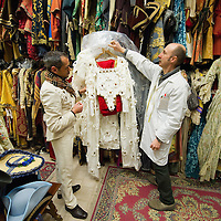 VENICE, ITALY - JANUARY 20: Choreographer Raffaele Dessi (L) and tailor Francesco Briggi (R) of the historic atelier Pietro Longi examine an Elizabeth I costume on January 20, 2012 in Venice, Italy. This is one of the busiest periods of the year for the atelier as the next few weeks the streets and canals of Venice will be filled with people attending the carnival,  wearing highly-decorative and imaginative carnival costumes and masks.