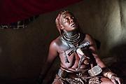 Himba woman inside her hut with ochre hair. Himba village, Kaokoveld, Namibia, Africa
