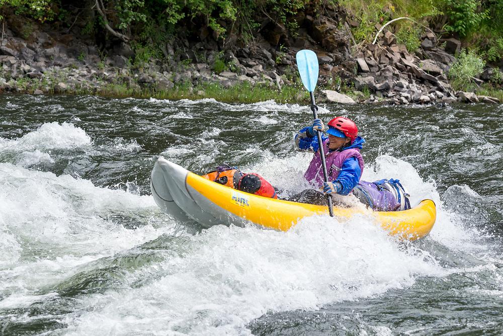 Woman paddling an inflatable kayak on Oregon's Grande Ronde River.