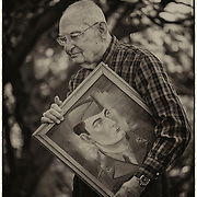 Robert Garrett of North Kansas City, 90, held a portrait of himself as a sergeant, radar operator, in the 142nd AAA (anti-aircraft artillery) gun battalion, painted by a German prisoner held by his unit, who traded the portrait for Garrett's cigarette rations.