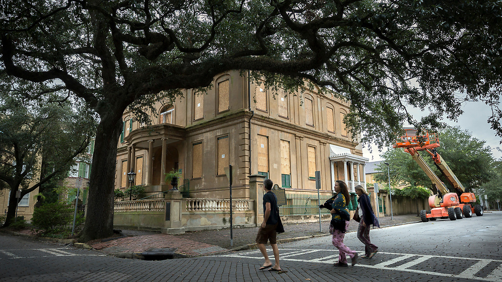 A group of evacuees from Ft. Lauderdale, Fla., walk past the Historic Owens-Thomas House museum, Sunday, Sept., 10, 2017 in downtown Savannah, Ga. Savannah and surrounding areas evacuated early Saturday morning in anticipation of early forecast of Hurricane Irma coming up the east coast. (AP Photo/Stephen B. Morton)