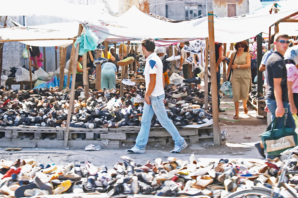 Street scene with market stalls, selling shoes in large quantities. Shkodra. Albania, Balkan, Europe.