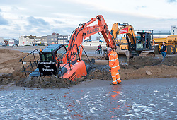 © Licensed to London News Pictures; 05/01/2021; Weston-super-Mare, UK. A mechanical excavator 'digger' has got stuck in the mud on the beach. Contractors were moving sand around the beach when first a dump truck got stuck and then the excavator got stuck trying while freeing the truck. Another excavator arrived to help dig it out. The tide is due in around 11pm tonight. Photo credit: Simon Chapman/LNP.