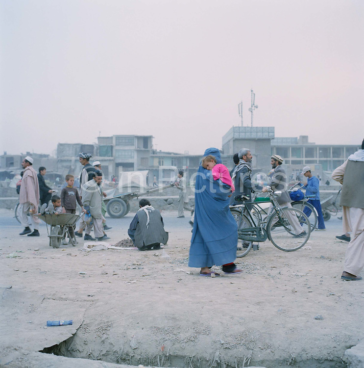Street life in Murad khane, Kabul. The Burkha is still a common site in Kabul with the influence of the Taliban still  very strong .