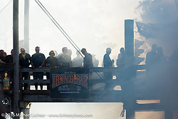 Another burn-out fills the sky at the Iron Horse Saloon during the Daytona Bike Week 75th Anniversary event. FL, USA. Sunday March 6, 2016.  Photography ©2016 Michael Lichter.