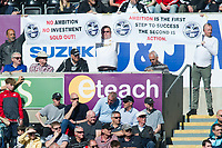 Football - 2017 / 2018 Premier League - Swansea City vs. Stoke City<br /> <br />  fans  in the crowd hold two  banners saying 'no ambition no investment sold out ' and 'ambition is the fist step to success the 2nd is action',  , at The Liberty Stadium.<br /> <br /> COLORSPORT/WINSTON BYNORTH