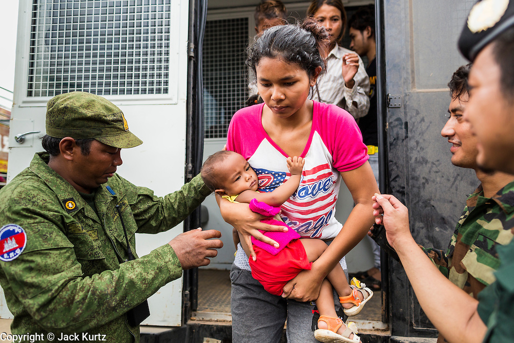 16 JUNE 2014 - POIPET, CAMBODIA: Cambodian soldiers help a woman and her child get out of a Thai immigration police truck in Poipet, Cambodia. More than 150,000 Cambodian migrant workers and their families have left Thailand since June 12. The exodus started when rumors circulated in the Cambodian migrant community that the Thai junta was going to crack down on undocumented workers. About 40,000 Cambodians were expected to return to Cambodia today. The mass exodus has stressed resources on both sides of the Thai/Cambodian border. The Cambodian town of Poipet has been over run with returning migrants. On the Thai side, in Aranyaprathet, the bus and train station has been flooded with Cambodians taking all of their possessions back to Cambodia.   PHOTO BY JACK KURTZ