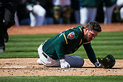 Oakland Athletics left fielder Matt Joyce (23) lays on the ground after hitting a foul ball off his leg during an exhibition game against the San Francisco Giants at Oakland Coliseum in Oakland, California, on March 25, 2018. (Stan Olszewski/Special to S.F. Examiner)