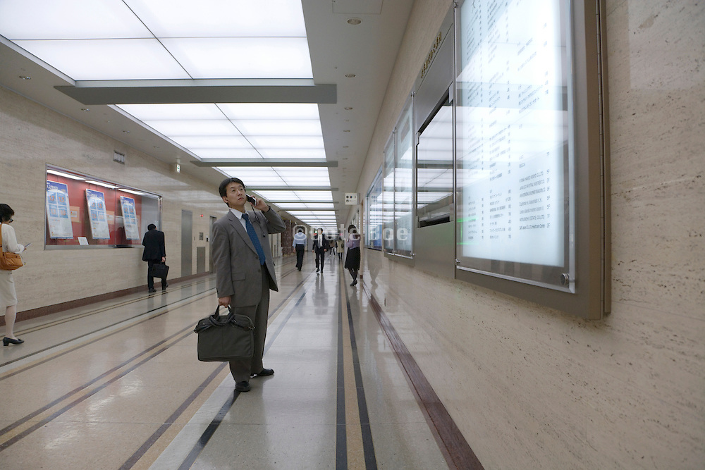 businessman looking at company directory board while talking on his cellphone Otemachi financial district in Tokyo
