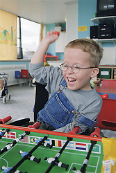 Young boy with Cerebral Palsy sitting in wheelchair playing table football on Children's ward in hospital,