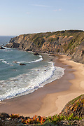 Secluded sandy beach in bay between rocky headlands at Parque Natural do Sudoeste Alentejano e Costa Vicentina, Natural Park, landscape view on the Ruta Vicentina long distance walking trail, at Praia dos Machados,  Carvalhal, Alentejo Littoral, Portugal, southern Europe