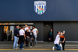 Fans outside the ground next to a West Bromwich Albion crest