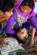 Lakshmi Tharu (in purple), 22, cradles her younger of 2 sons aged 10 and 4 as she gathers with other child mothers and child brides to see Pahari Tharu, 52, the female community health worker in Bhaishahi village, Bardia, Western Nepal, on 29th June 2012. Lakshmi has never been to school and was married to an 11 year old boy when she was nine, giving birth to her first child when she was 12. In Bardia, StC works with the district health office to build the capacity of female community health workers who are on the frontline of health service provision like ante-natal and post-natal care, and working together against child marriage and teenage pregnancy especially in rural areas. Photo by Suzanne Lee for Save The Children UK
