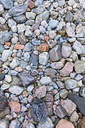 Pastel shades and various sizes of granite rocks and pebbles on beach on shoreline of Loch Linnhe in Western Scotland, UK